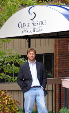 Andrew Graham in front of Clinic Service office